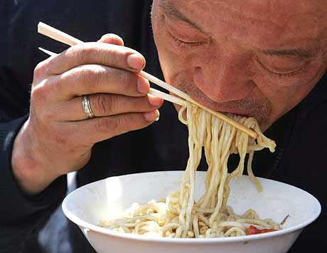 En kinesisk mann benytter seg av engangsspisepinner på en restaurant i Beijing i dag. (Foto: AP/Scanpix)