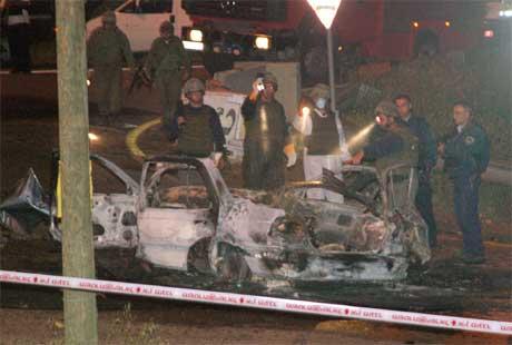 Israelske soldater undersøker bilvraket etter selvmordsaksjonen i går kveld. (Foto: AP/Scanpix)