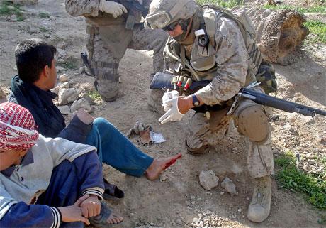 <b>Kamp om opinionen:</b> Dette bildet sendte de amerikanske styrkene i Irak ut i dag. Det viser en soldat som hjelper en iraker med plaster. (Foto: USAs militære styrker/AFP/Scanpix)