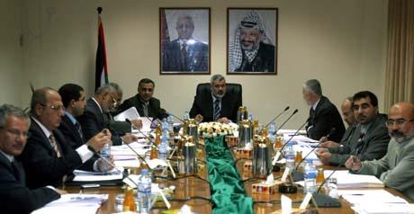 Den nye regjeringen under portrettet av presidentene Yassir Arafat og Mahmourd Abbas (t.h.) (Foto: K.Hamra, AP)