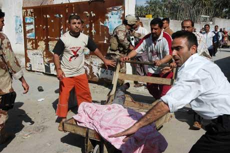 Et av ofrene for selvmordsbomberne blir brakt bort (Scanpix/AP)
