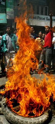 Demonstrantene danset rundt brennende bildekk mens de ropte slagord mot kongen. (Foto: Scanpix/AP)