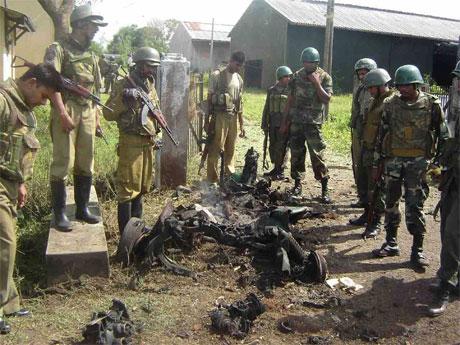 Politi inspiserer det som er igjen av soldatenes kjøretøy etter eksplosjonen i Vavunyia i dag. (Foto: Reuters/Scanpix)