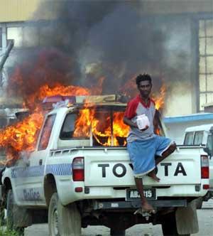 Biler står i brann i hovedstaden Honiara i protest mot den hemmelige avstemningen i parlamentet i dag. (Foto: Reuters/Scanpix)
