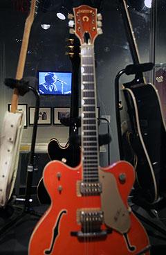 En videofilm surrer og går fra en Roy Orbison-konsert bak utstilte Orbison-gitarer i Rock and Roll Hall of Fame i Cleveland. Foto: AP / Scanpix.