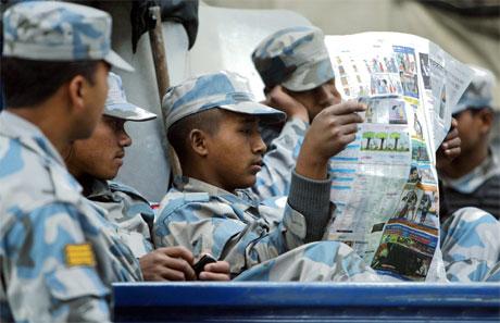 Nepalske soldatar slappar av med avislesing, men situasjonen i Katmandu er langt frå roleg. (Foto: AFP/Scanpix)