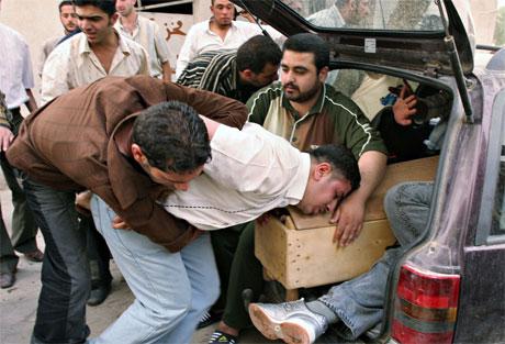 En slektning klamrer seg til kisten til en av de som ble drept av bomber i Bagdad i dag. (Foto: AP/Scanpix)