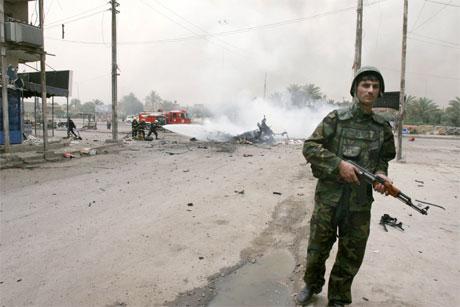 En soldat sikrer området etter en eksplosjon i Bagdad i dag. (Foto: AP/Scanpix)