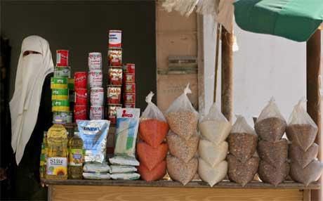 En palestinsk kvinne i Gaza går forbi en butikk som selger mat gitt av USA og EU. Krisen i den palestinske økonomien er nå verre enn forutsett. (Foto: Khalil Hamra/ AP/ Scanpix)