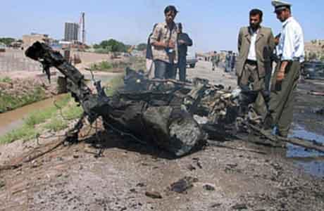 Afgahnere samlet rundt en bil som ble ødelagt av en selvmordsbombe i Herat. Foto: Ahmad Fahim , Reuters