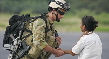 En australsk soldat tar en øst-timorsk dame i hånden etter å ha landet på flyplassen i Dili (Foto: AP/Scanpix)