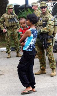 En mor bærer barnet sitt forbi australske soldater i Øst-Timor. Håpet er at de utenlandske styrkene vil kunne stabilisere situasjonen i det fattige landet. Foto: Reuters/Lirio Da Fonseca