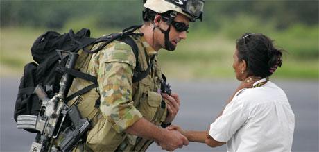 En australsk soldat håndhilser på en kvinne fra Øst-Timor etter å ha ankommet flyplassen i byen Dili torsdag.