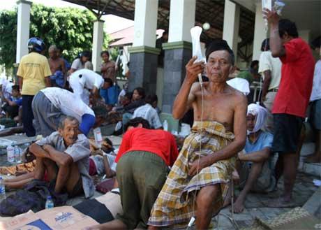 Lettere skadde jordskjelvofre får hjelp ute på gata i Yogykarta. Et norsk feltsykehus er nå på vei. (Foto: AP/Scanpix)