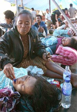 En kvinne gir vann til en skadet slektning i en provisorisk leir for etter skjelvet. (Foto: AFP/Scanpix)