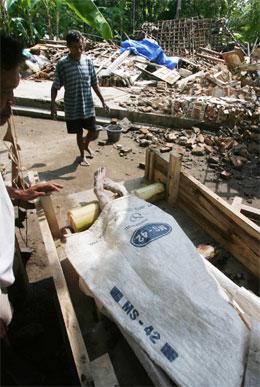 Eit offer for jordskjelvkatastrofen blir frakta bort for å bloi gravlagd. (Foto: AFP/Scanpix)