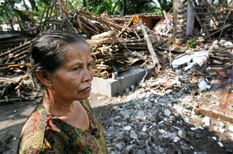 Ei kvinne står framfor restane av det som ein gong var heimen hennar. (Foto: AFP/Scanpix)