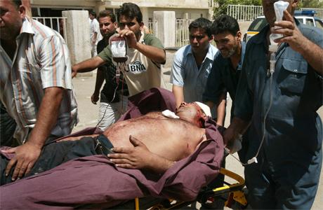 En skadet mann blir brakt til sykehus etter at en selvmordsbomber drepte 13 personer og skadet flere i Irak 26 mai. (Foto: AP, Scanpix)