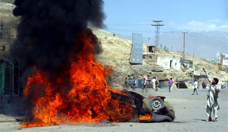 En afghansk protestant kaster stein mot politiet. Foto: AP Photo/Xinhua, Zabi Tamanna