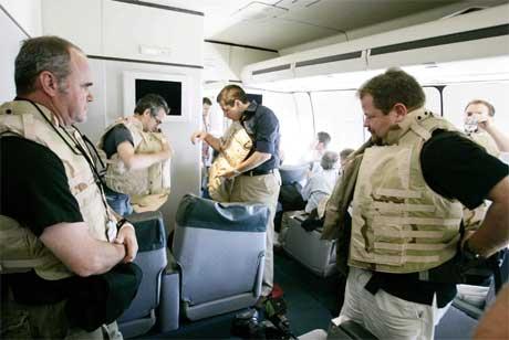 Journalister om bord på presidentflyet Air Force One tar på seg skuddsikre vester før flyet lander i Bagdad. (Foto: Larry Downing/Reuters/Scanpix)