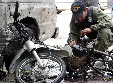 SMELLER: En politimann sjekker åstedet for en av bombene som gikk av i provinsen Pattani Foto: AFP/Scanpix.