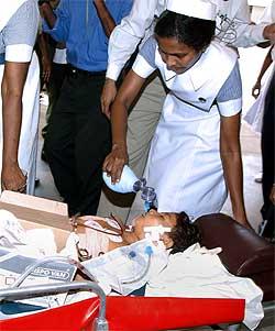 SÅRET: Den 10 år gamle jenta Pavithra overlevde og hjelpes av en sykepleier. Foto: AFP/Scanpix.