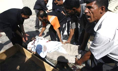 Slektninger løfter et av ofrene opp i kisten. (Foto: Reuters/Scanpix)