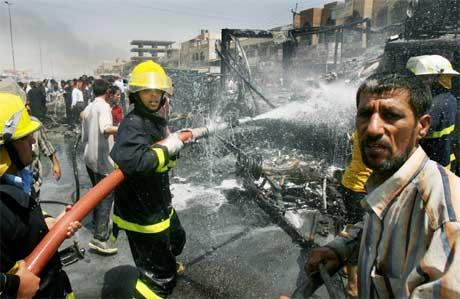 Irakiske brannmenn i aksjon enner eksplosjon i et utendørs marketi Bagdad. (Foto. Ap/Scanpix)