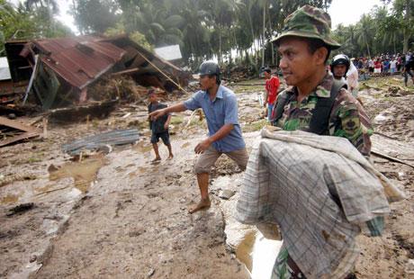En soldat bærer et omkommet barn på den flom- og rasrammede øya Sulawesi( Scanpix/Reuters)