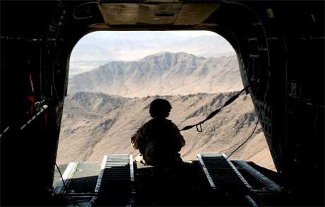 En amerikansk soldat ser ut fra et helikopter over Helmand-provinsen. På bakken er over 100 mennesker drept i kamper de siste tre dagene. (Foto: Rodrigo Abd/ AP/ Scanpix)