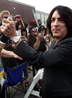 Kiss-vokalist Paul Stanley hilste på fansen som hadde møtt fram for å overvære åpningen av KISS Coffeehouse. For anledningen var sminken tørket av. Foto: AP / Scanpix.