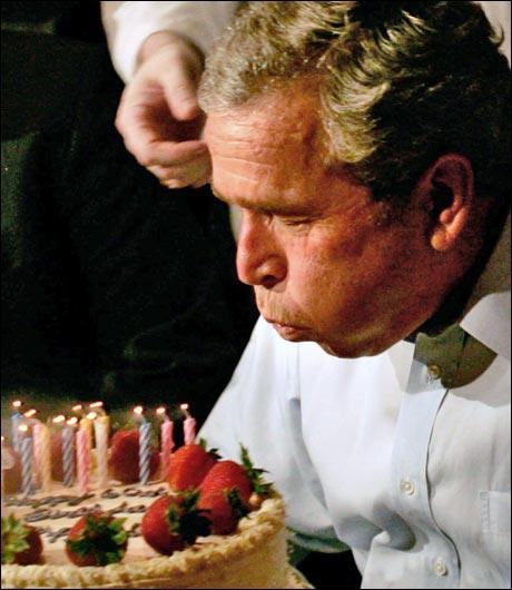 Mission accomplished: Vi vet ikke om bildene er tatt samtidig, eller om Bush ble sittende på denne måten utover kvelden. (foto: Scanpix / AFP)