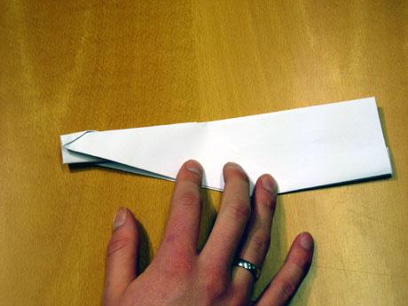 11. Her har eg bretta ned vengane på begge sider. Legg merke til den vesle papirkanten som er komen i midten, det er han du skal halde i når du sender flyet.