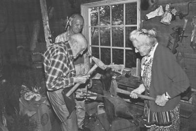 Demonstrasjon av ljåsmiing på Lungård i Hornindal. Ragnhild og Rasmus Lungård med sleggene, medan Petter Lødemel ser på. Foto: Randi Lødøen Sømme