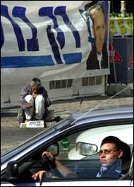 """En tigger sitter ved en plakat av Israels statsminister Ehud Barak i Tel Aviv. På plakaten står det """"Bare Barak"""", på tiggerens boks står det """"Jeg føler trygget med Sharons fred"""". (Foto: AP)"""