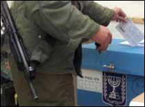En israelsk soldat avgir sin stemme mandag ved en militærpost ved Bet El, nær Ramallah. (Foto: Reuters)