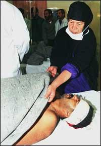 En sykepleier bretter et pledd over en mann som skal ha blitt skadet under det britiske/amerikanske angrepet på mål utenfor Bagdad fredag kveld. (Foto: EPA)