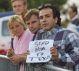 """""""Send ham til Texas"""", står det på plakaten som en tilskuer holder foran Scheveningen-fengselet i Haag i går kveld. I natt kom Milosevic til fengselet. (Foto: Scanpix/AP/Michel Porro)"""